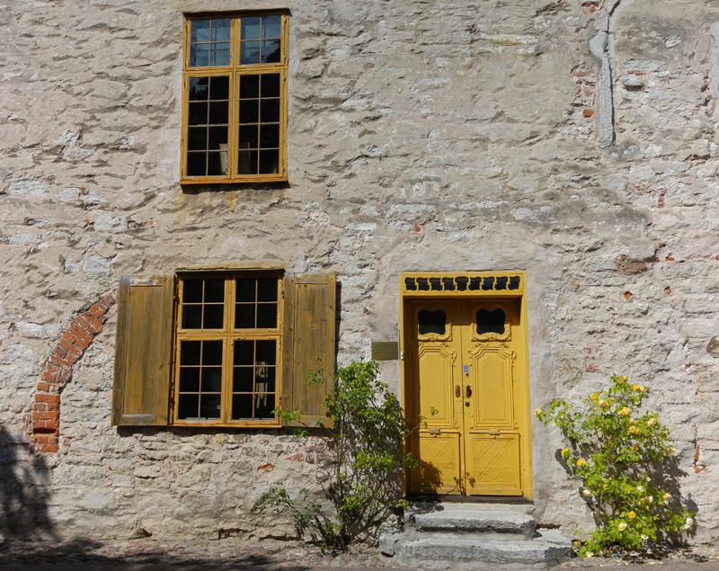 Medeltida stenhus i Visby med gulmålad trädörr och spröjsade fönster