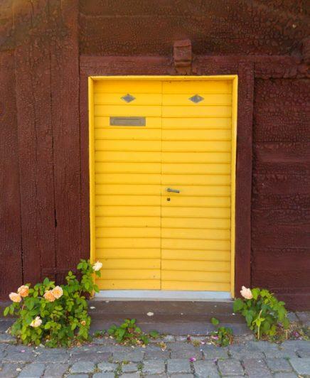 Gul dörr med rosor på gammalt hus i Visby